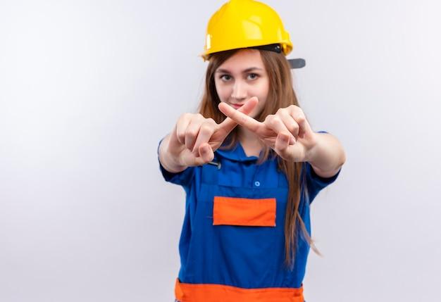 Młoda kobieta budowniczy pracownik w mundurze budowy i hełmie ochronnym, dzięki czemu obronę gest krzyżuje palce wskazujące stojąc nad białą ścianą