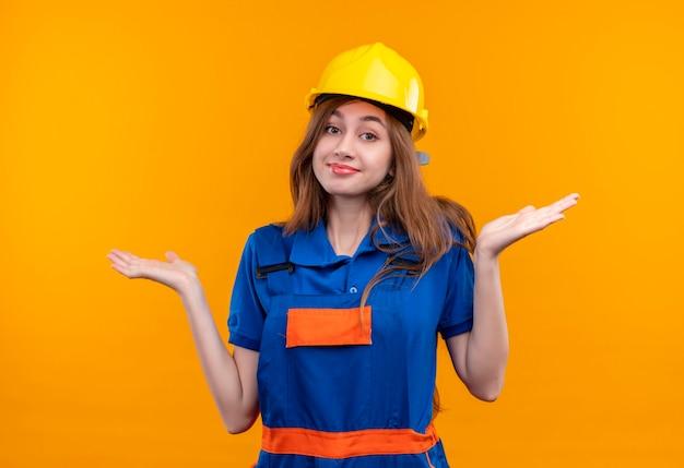 Młoda kobieta budowniczy pracownik w mundurze budowy i hełmie ochronnym patrząc zdezorientowany uśmiechnięty wzruszając ramionami, nie mając odpowiedzi stojącej