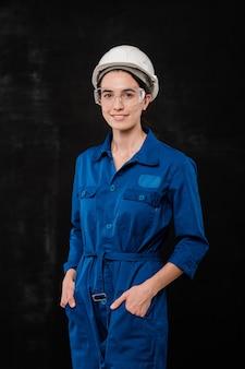 Młoda kobieta budowniczy w kasku i niebieskim kombinezonie, trzymając ręce w kieszeniach, stojąc przed kamerą w izolacji
