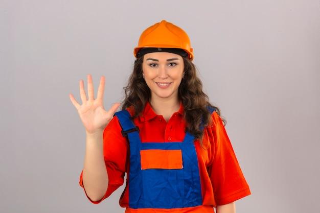 Młoda kobieta budowniczy w mundurze budowlanym i kasku ochronnym uśmiechnięta wesoło, pokazująca i wskazująca palcami numer pięć, wyglądająca pewnie i szczęśliwie