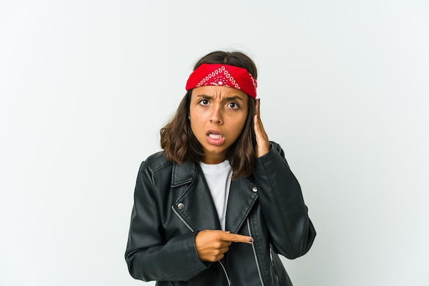 Młoda kobieta bujaka na białej ścianie zapominając o czymś, uderzając dłonią w czoło i zamykając oczy