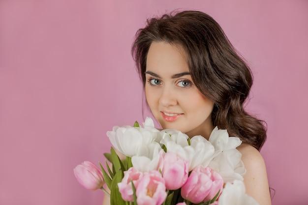 Młoda kobieta bukiet tulipanów uśmiechnięta dziewczyna portret wiosna różowa ściana