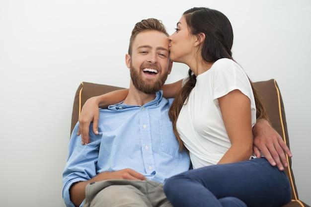 Młoda kobieta całuje mężczyznę z pasją