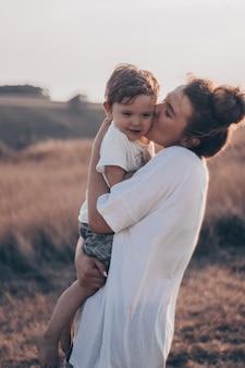 Młoda kobieta całuje swojego małego synka w słońcu na łące o zachodzie słońca. młoda matka trzyma swoje dziecko. matka i synek miło spędzają czas na łonie natury. obraz stonowanych kolorów