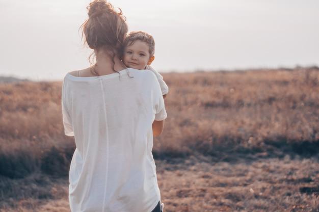 Młoda kobieta całuje swojego małego synka w słońcu na łące o zachodzie słońca. młoda matka trzyma swoje dziecko. matka i synek miło spędzają czas na łonie natury.