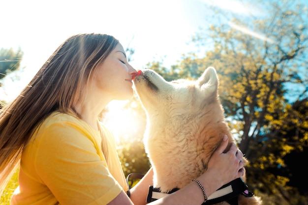 Młoda kobieta całuje swojego psa w parku o zachodzie słońca