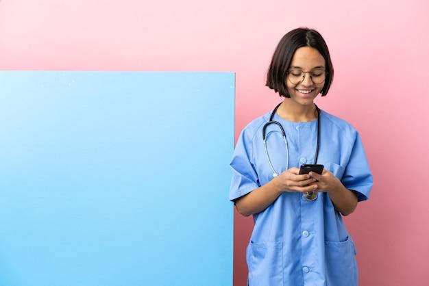 Młoda kobieta chirurg rasy mieszanej z dużym banerem na białym tle wysyłanie wiadomości z telefonu komórkowego