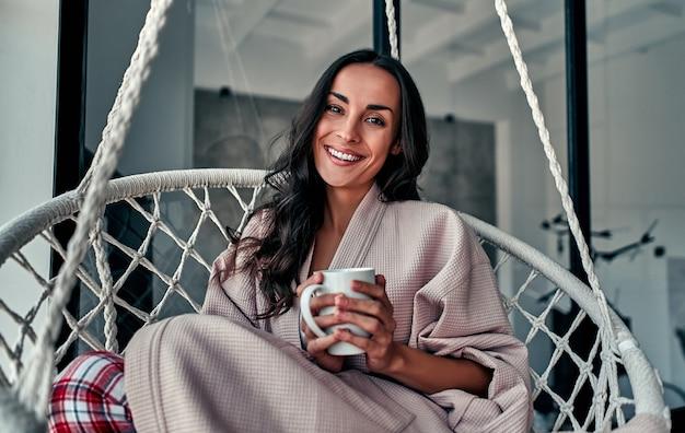 Młoda kobieta chłodzenie w domu w wygodnym wiszącym fotelu przy oknie z filiżanką kawy w ręku. dziewczyna relaks w huśtawce w salonie na poddaszu na sobie domowy szlafrok.