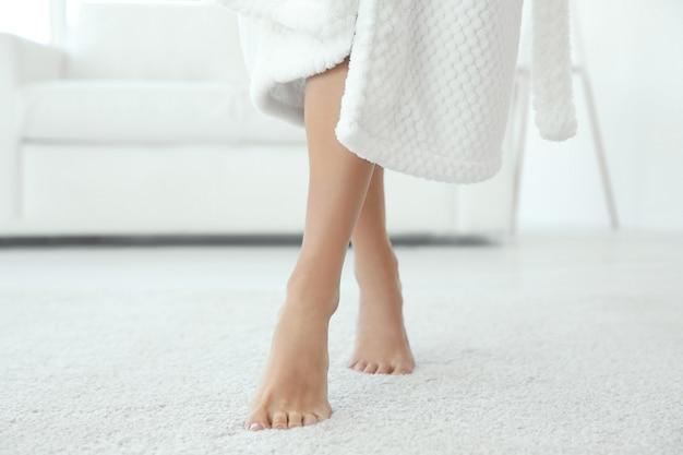 Młoda kobieta chodząca po podłodze po prysznicu