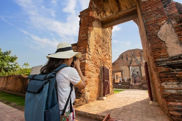 Młoda kobieta chodzi w starej świątyni w phra nakhon si ayutthaya, tajlandia na relaksujący dzień.