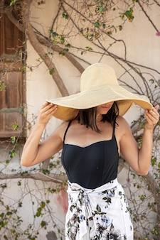 Młoda kobieta chowa się przed słońcem pod dużym słomkowym kapeluszem przy ścianie oplecionej suchymi gałęziami kwitnącego drzewa