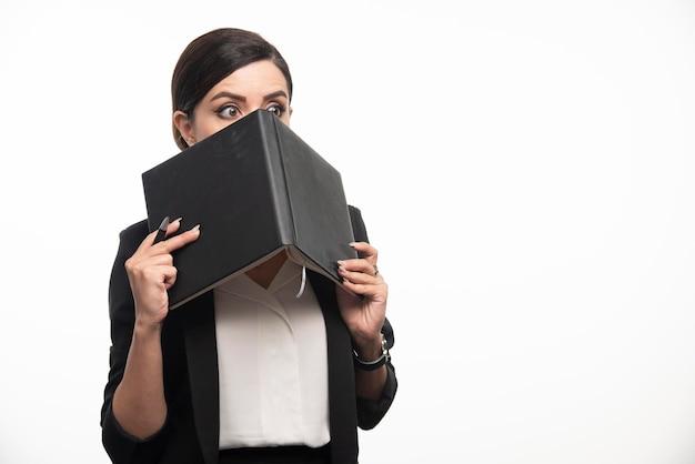Młoda kobieta chowa się za książką na białym tle. zdjęcie wysokiej jakości
