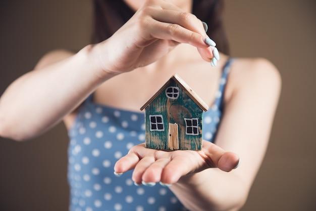 Młoda kobieta chroniąca dom w rękach