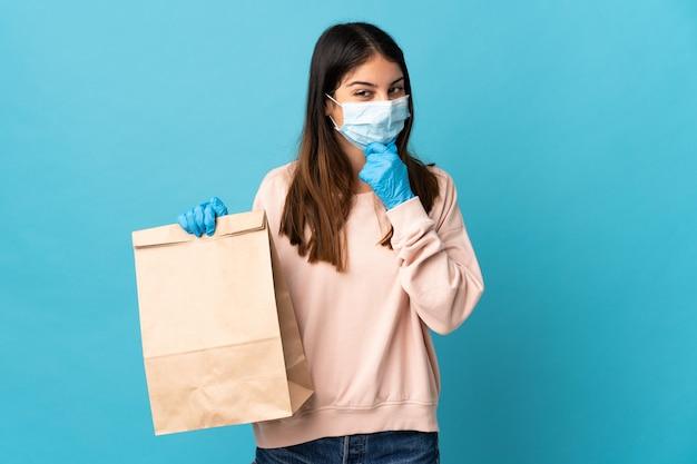 Młoda kobieta chroniąca przed koronawirusem z maską i trzymająca torbę na zakupy na niebieskiej ścianie myśli o pomyśle i patrząc z boku