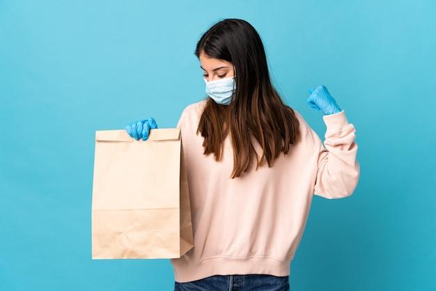 Młoda kobieta chroniąca przed koronawirusem z maską i trzymająca torbę na zakupy na niebieskiej ścianie świętuje zwycięstwo