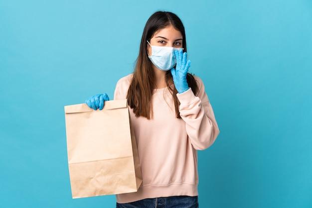 Młoda kobieta chroniąca przed koronawirusem z maską i trzymająca torbę na zakupy na niebiesko, krzycząca z szeroko otwartymi ustami