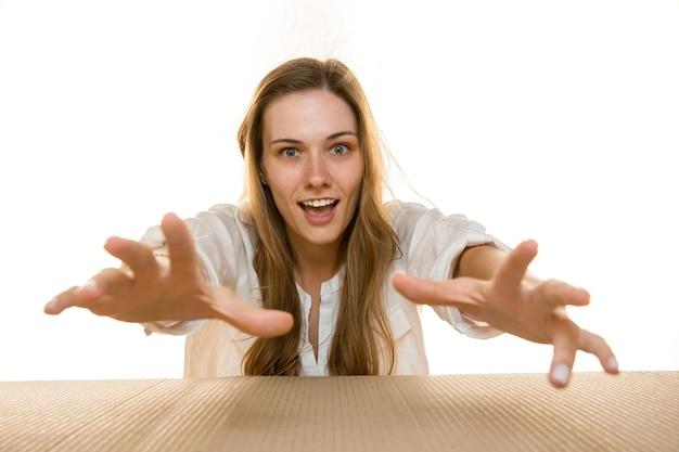 Młoda kobieta chwyta coś z przodu na drewnianym stole