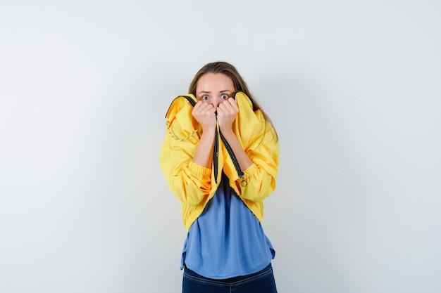 Młoda kobieta ciągnąc kołnierz na twarzy w t-shirt, kurtkę i patrząc przestraszony. przedni widok.