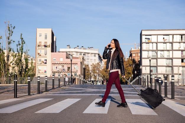 Młoda kobieta, ciągnąc walizkę, rozmawia przez telefon