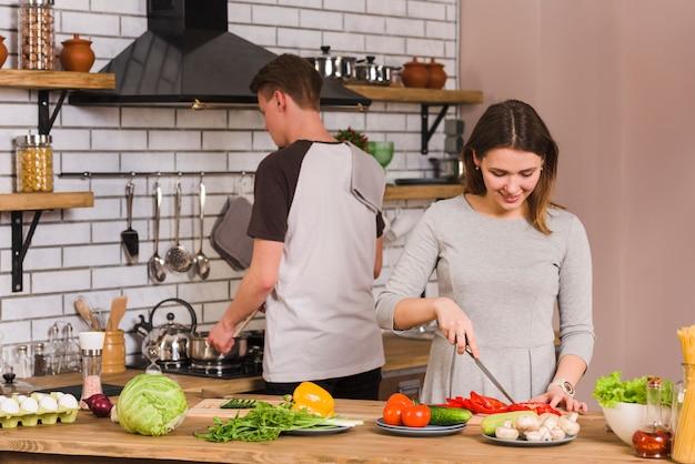 Młoda kobieta cięcia warzyw w pobliżu chłopaka