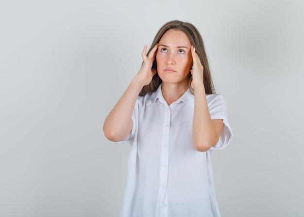 Młoda kobieta cierpi na ból głowy w białej koszuli i wygląda na zmęczoną