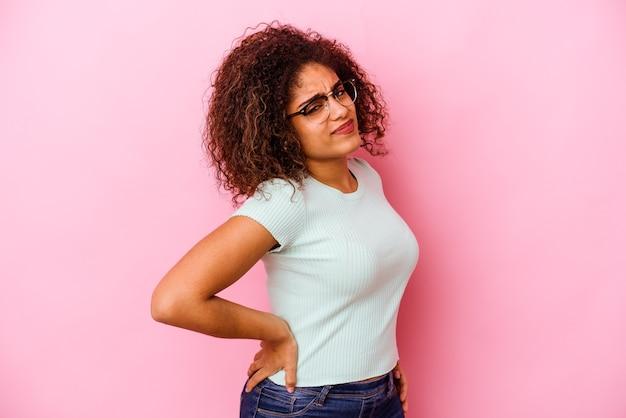 Młoda kobieta cierpi na ból pleców na białym tle na różowej ścianie