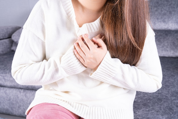 Młoda kobieta cierpi na ból serca, siedząc na kanapie w domu