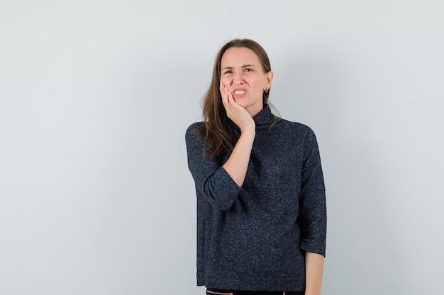 Młoda kobieta cierpi na ból zęba w koszuli i wygląda niewygodnie