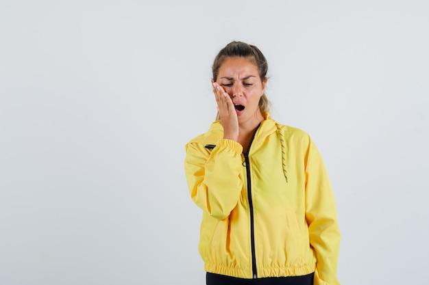 Młoda kobieta cierpi na ból zęba w żółtym płaszczu przeciwdeszczowym i wygląda na bolesną