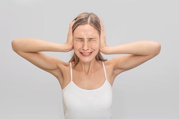 Młoda kobieta cierpi na bóle głowy. zakrywa uszy rękami i trzyma oczy zamknięte. młoda kobieta nosi biały t-shirt.