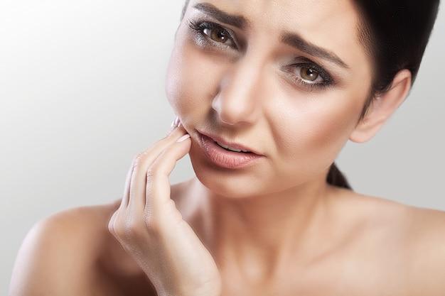 Młoda kobieta cierpi na okropny ból w zębach