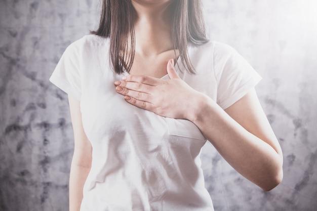 Młoda kobieta cierpi na silny ból w klatce piersiowej