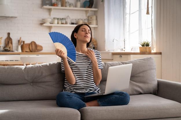 Młoda kobieta cierpi na udar cieplny, macha wentylatorem i siedzi na kanapie w domu