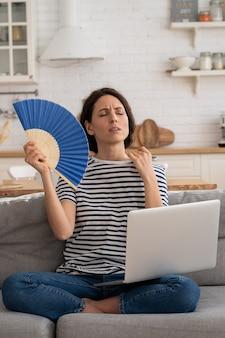 Młoda kobieta cierpi na udar cieplny mieszkanie bez klimatyzacji wymachującej wentylatorem siedząca na kanapie w domu