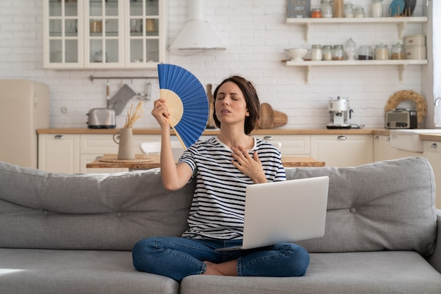 Młoda kobieta cierpi na udar cieplny siedząc na kanapie w domu