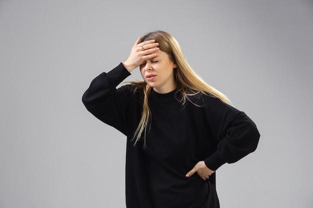Młoda kobieta cierpi z powodu bólu, czuje się chora, chora i osłabiona w izolacji w studio