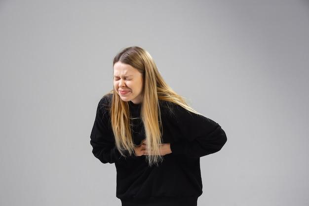 Młoda kobieta cierpi z powodu bólu, czuje się chora i osłabiona na ścianie is