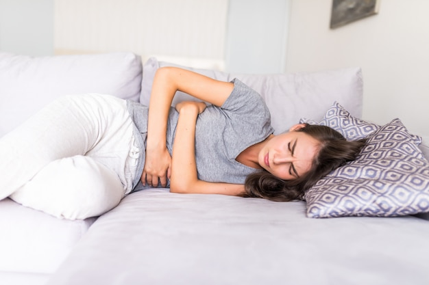 Młoda kobieta cierpiąca na ból brzucha z powodu miesiączki leżąc na kanapie i trzymając się za brzuch.