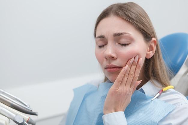 Młoda kobieta cierpiąca na ból zęba czeka na leczenie stomatologiczne w klinice