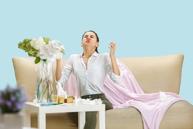 Młoda kobieta cierpiąca na kurz domowy lub alergię sezonową. kichanie w serwetce i siedzenie w otoczeniu zużytych serwetek na podłodze i sofie. przyjmowanie leków bez rezultatu. pojęcie opieki zdrowotnej.