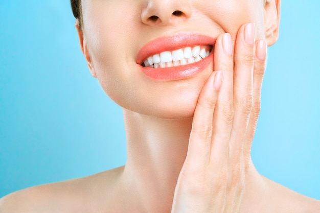 Młoda kobieta cierpiąca na silny ból zębów dotykających ręką policzka.