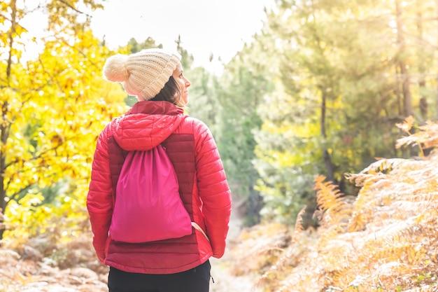 Młoda kobieta, ciesząc się jesień na zewnątrz. dziewczyna piesze wycieczki w góry.