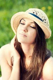 Młoda kobieta, ciesząc się latem w parku