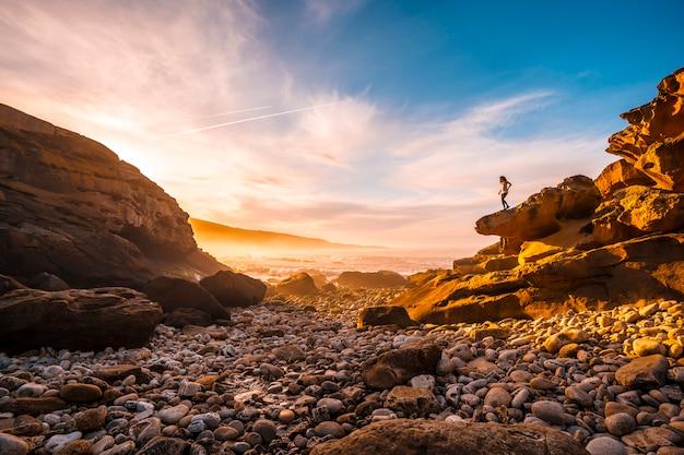 Młoda kobieta, ciesząca się pomarańczowym zachodem słońca na wybrzeżu góry jaizkibel w pobliżu san sebastian, gipuzkoa. hiszpania