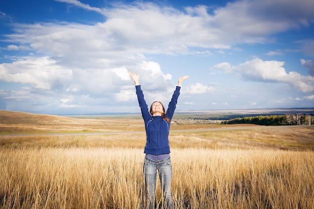 Młoda kobieta ciesząca się przyrodą z rękami podniesionymi do nieba