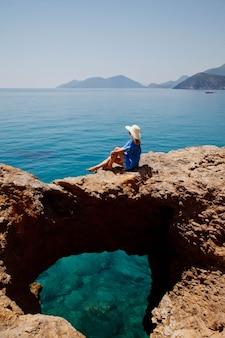 Młoda kobieta ciesząca się wakacjami na skale z luksusowym widokiem spacerującym pokazującym emocje na lazurowym tle morza