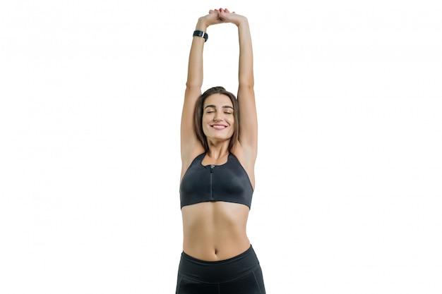 Młoda kobieta cieszy oczy sportowe zamknięte, w czarnej odzieży sportowej, na białym tle