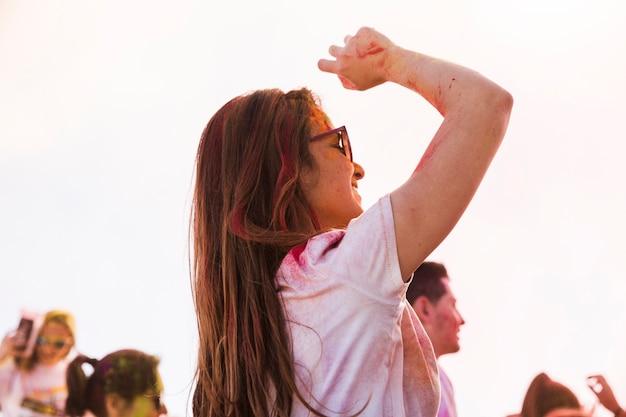 Młoda kobieta cieszy się i tanczy w holi z kolorami