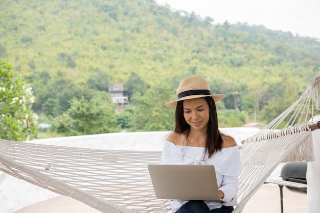 Młoda kobieta cieszy się laptopa w hamaku na plaży