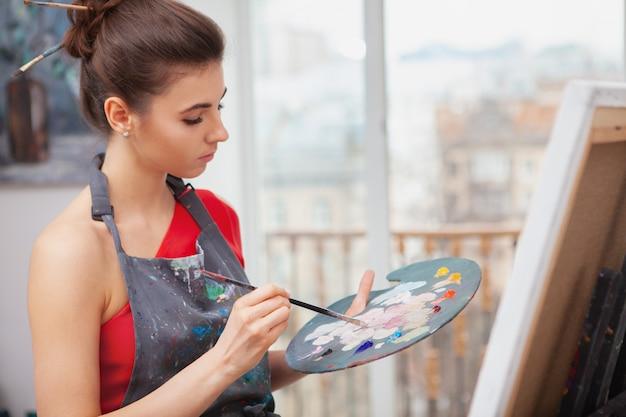 Młoda kobieta cieszy się malować przy jej sztuki studiiem